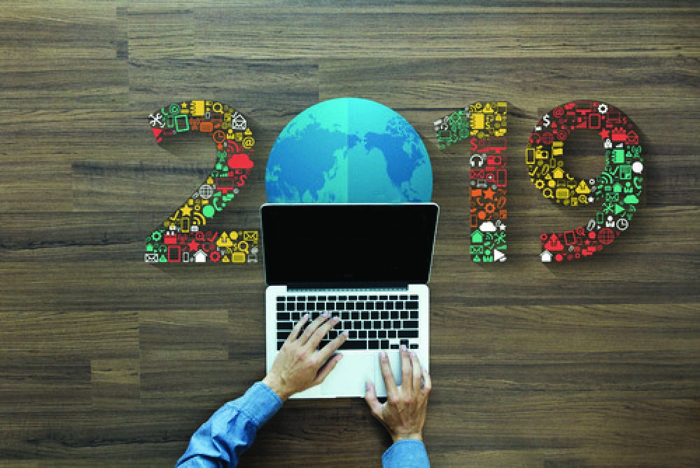 2019 spelled out with multi-colored flowers. A globe replaces the 0. A persons hands are visible on the laptop.