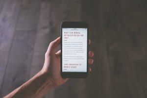 picture of persons hand holding mobile phone withe website text about how mobile optimization can help your business